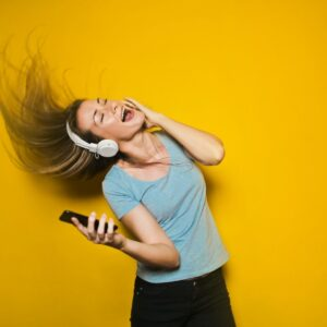 woman in blue shirt listening to music