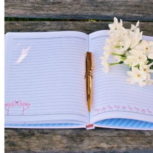 Book with gold pen and white flowers